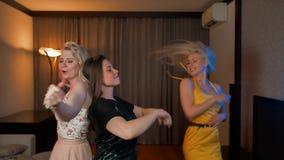 Tre ragazze di risata che ballano insieme nella casa al partito stock footage