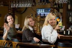 Tre ragazze graziose ad un contatore della barra Fotografia Stock