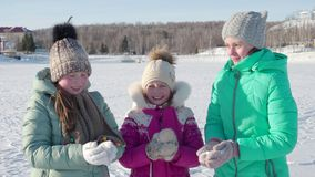 Tre ragazze in guanti e cappelli gettano felicemente la neve su su una passeggiata un giorno di inverno 4K video d archivio