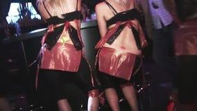 Tre ragazze nel grembiule della cameriera di bar, ballo superiore nero sul partito in night-club intrattenimento Bottino di scoss stock footage