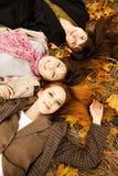 Tre ragazze nella sosta di autunno. Immagini Stock
