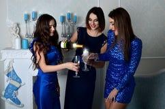 Tre ragazze riempiono il vetro di champagne immagini stock libere da diritti
