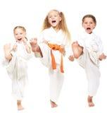 Tre ragazze si sono vestite in kimono bianco eseguono la perforazione Fotografia Stock
