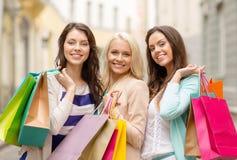 Tre ragazze sorridenti con i sacchetti della spesa in ctiy Immagine Stock Libera da Diritti