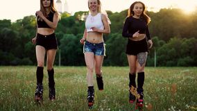 Tre ragazze in stivali con le molle che passano l'estate parcheggiano al tramonto che fa gli sport stock footage