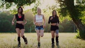 Tre ragazze in stivali con le molle che passano l'estate parcheggiano al tramonto che fa gli sport archivi video