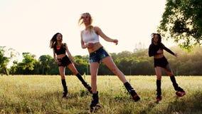 Tre ragazze in stivali sulle molle si esercitano brucianti grassi nell'addestramento del gruppo archivi video