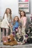 Tre ragazze sveglie che aspettano il Natale Immagini Stock