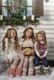 Tre ragazze sveglie che aspettano il Natale Immagine Stock