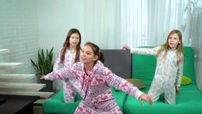Tre ragazze sveglie in pigiami che ballano a casa archivi video