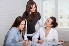 Tre ragazze in vestiti convenzionali che firmano i documenti di affari Fotografia Stock