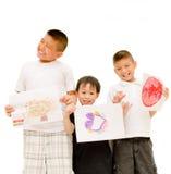 Tre ragazzi asiatici che mostrano la loro illustrazione Fotografie Stock Libere da Diritti
