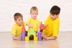 Tre ragazzi che giocano sul pavimento contro un muro di mattoni bianco immagini stock