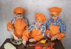 Tre ragazzi europei svegli in costumi arancio cucinano per preparare l'insalata di verdure immagine stock