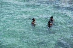 Tre ragazzi locali che nuotano nel mare, Sri Lanka Fotografia Stock