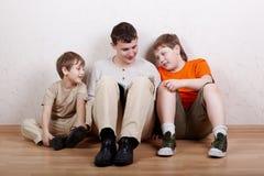 Tre ragazzi si siedono e leggono il libro Immagine Stock Libera da Diritti