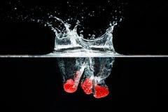 Tre raspberrysnedgångar djupt under vatten med en stor färgstänk royaltyfria foton