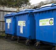 Tre recipienti di riciclaggio blu che stanno in una linea Fotografia Stock
