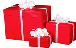 Tre regali di Natale con gli archi del nastro isolati Fotografia Stock