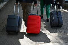 Tre resväskor som dras på trottoaren i staden arkivfoton