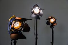Tre riflettori dell'alogeno con le lenti di Fresnel su un fondo grigio Fotografando e filmare nell'interno fotografia stock