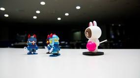 Tre robotic vakter är församlade med blåa hjälmar med röda horn att komma med ner en vit björn med en rosa godis som inkräktar on royaltyfri foto