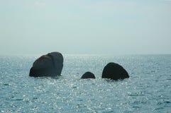 Tre rocce scure che aumentano da un oceano scintillante Immagine Stock Libera da Diritti