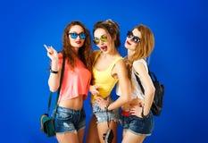 Tre roliga Hipsterflickor på blå bakgrund Fotografering för Bildbyråer