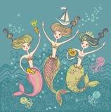 Tre roliga sjöjungfruar. Arkivbild