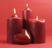 Tre romantiska röda tände stearinljus mot en röd bakgrund. Arkivfoto