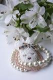Tre rosa e braccialetti bianchi con la fibula e fiori bianchi Immagini Stock