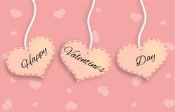 Tre rosa hjärtor med lycklig bokstäver för dag för valentin` s Arkivfoton