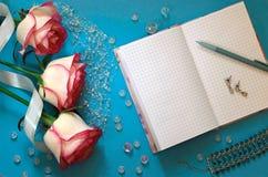 Tre rosa rosor, en tom anteckningsbok, pärlor, ett armband på en blått royaltyfri bild