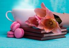 Tre rosa tulpan, en kopp kaffe och tre rosa makron Arkivbilder