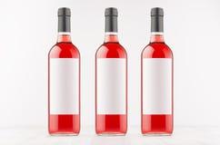 Tre rosa vinflaskor med tomma vitetiketter på det vita träbrädet, förlöjligar upp Arkivbild