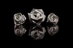 Tre rose di carta fatte dalle pagine del libro isolate sul nero Fotografie Stock