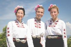 Tre Rose Festival flickor i nationell dräkt arkivbilder