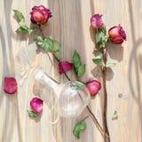 Tre rose rosa secche, petali sparsi del fiore, foglie verdi, vaso di vetro sulla fine di legno di vista superiore del fondo su fotografia stock libera da diritti