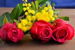 Tre rose rosse contro un fondo marrone immagini stock