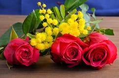 Tre rose rosse contro un fondo marrone immagine stock