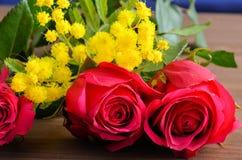 Tre rose rosse contro un fondo marrone fotografie stock