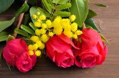 Tre rose rosse contro un fondo marrone immagine stock libera da diritti