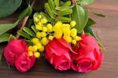 Tre rose rosse contro un fondo marrone Fotografia Stock