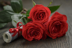 Tre rose rosse e mazzi di dollari Fotografia Stock