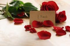Tre rose rosse e petali sulla vecchia tavola di legno con la carta di carta dell'8 marzo Fotografia Stock
