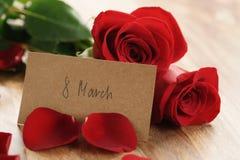 Tre rose rosse e petali sulla vecchia tavola di legno con la carta di carta dell'8 marzo Immagini Stock Libere da Diritti