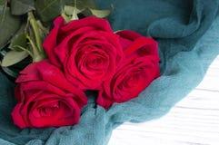 Tre rose rosse su fondo di legno bianco Fotografie Stock