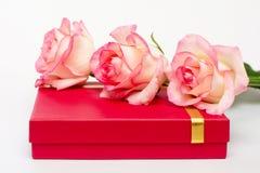 Tre rose si trovano sulla scatola bassa rossa Regali su un fondo bianco Un regalo per il caro fotografie stock libere da diritti