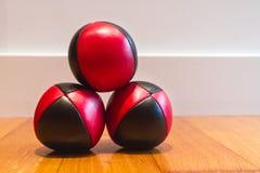 Tre rossi e palle da giocoliere nere immagini stock