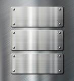 Tre rostfritt stålmetallplattor på borstat Royaltyfria Bilder